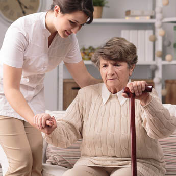 Old lady receiving assistance standing up with walking stick