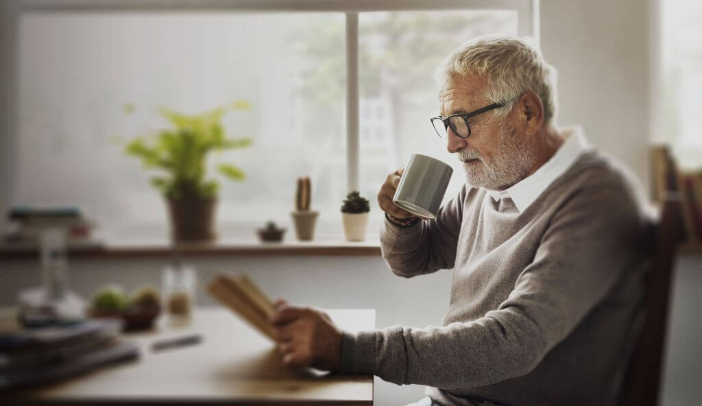 Old man drinking tea coffee reading paper