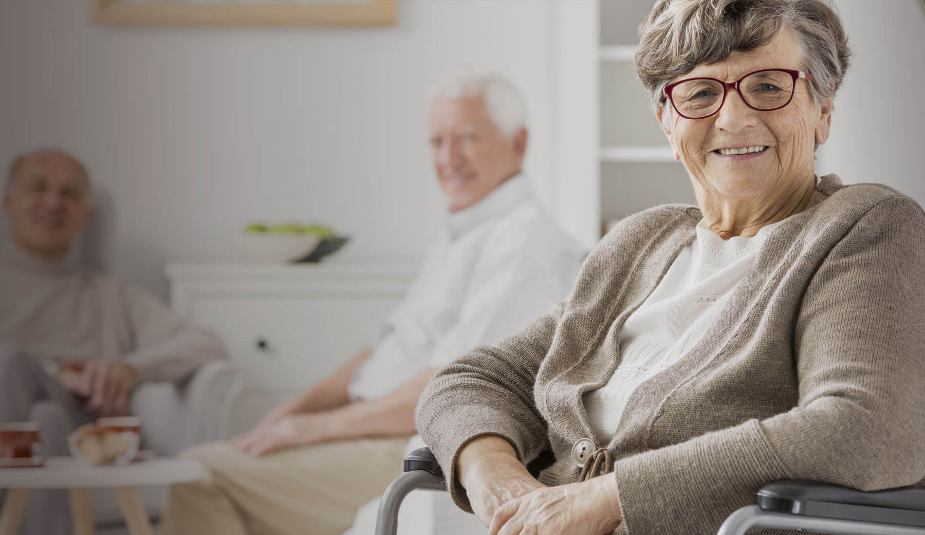 Old lady with glasses in wheelchair smiling